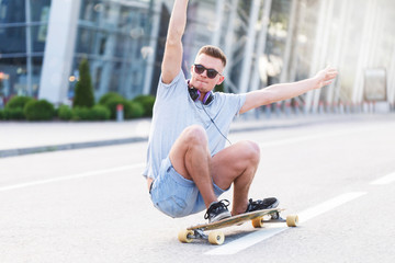 Skateboarder in sunglasses rides longboard on asphalt road before modern building in the city, low position trick ride