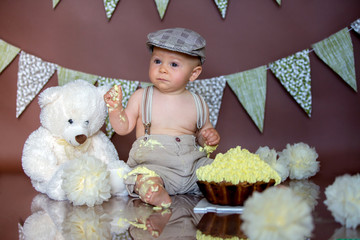 Little baby boy, celebrating his first birthday with smash cake party, studio isolated shot on brown