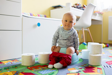 Smiling baby sitting on chamber pot with lots of toys and toilet paper around him