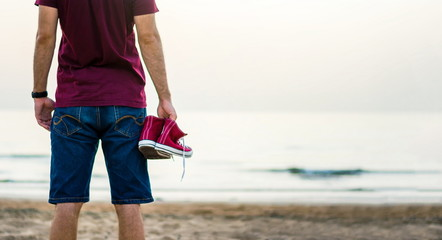 Man holding sneakers on the beach