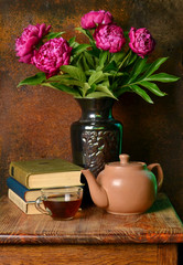 Beautiful lilac peonies in a vase, a Cup of tea, a kettle and books on a rust background.