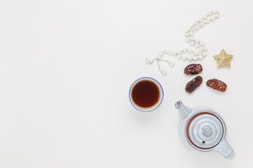 Table top view aerial image of decoration Ramadan Kareem holiday background.Flat lay dates with white rosary & cup tea.Halal meal set for fasting is obligatory for Muslim on white wooden and space.