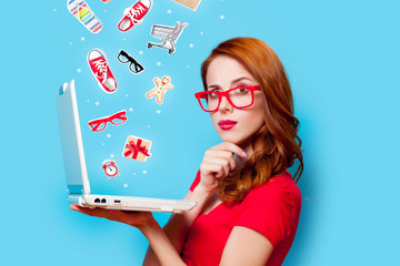 Young beautfiul redhead girl in eyeglasses with laptop computer on blue background