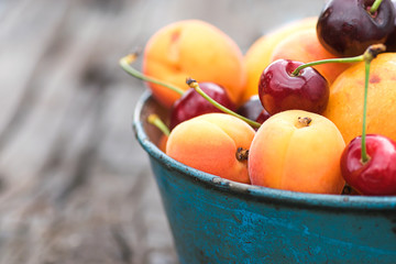 Summer berries and fruits. Apricots and cherries in a blue bowl. Close-up