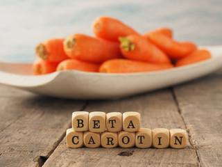 Holzwürfel mit dem Wort Beta Carotin, Frische Karotten im Hintergrund