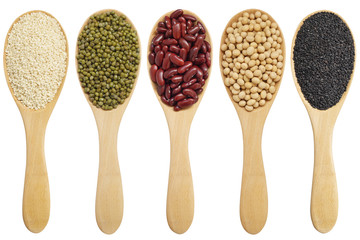 set of wooden spoons with cereal grains isolated on white background