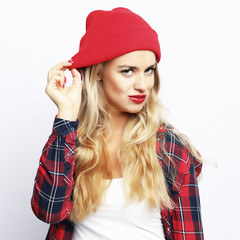 Lifestyle concept. hipster blonde woman with bright sexy make up wearing stylish urban plaid shirt and red hat