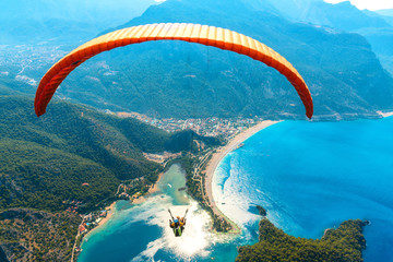 Paragliding in the sky. Paraglider tandem flying over the sea with blue water and mountains in bright sunny day. Aerial view of paraglider and Blue Lagoon in Oludeniz, Turkey. Extreme sport. Landscape Wall mural
