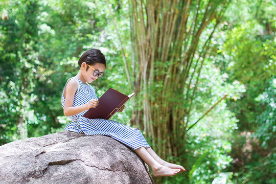 Asian little girl with glasses sitting on stone reading a books