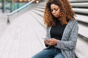 Portrait of young black woman using mobile phone