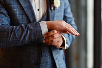A man in a stylish suit straightens cuffs on his shirt. Shooting of a businessman in a suit. Business concept. Close-up of a man in a tux fixing his cufflink. groom bow tie cufflinks.