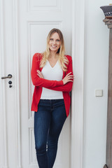 Young smiling woman standing by white door at home