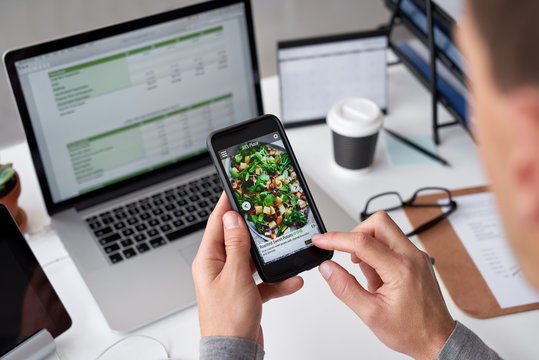 Man at work using a food ordering delivery app