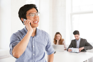 Happy young asian man talking on mobile phone