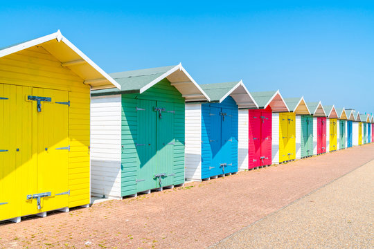 A row of colorful wooden beach huts on the beach in Eastbourne, East Sussex, UK