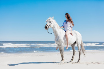 Aluminium Prints Wild West Girl sitting on a white horse by the sea