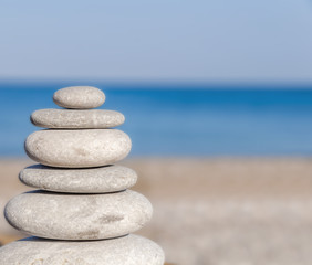 Printed roller blinds Zen Stress balanced several Zen stones on blurred blue sea and beach