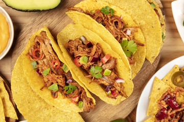 Closeup of Mexican tacos with pulled meat, avocado, chili peppers, cilantro