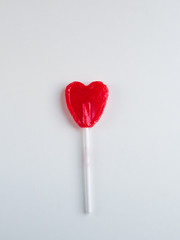 Red heart lollipop on white background