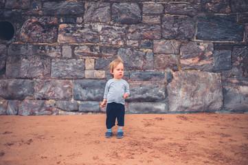 Little boy by big wall on the beach