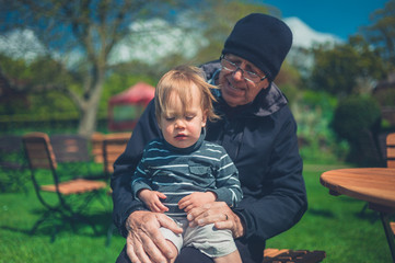 Grandfather and grandchild relaxing by table outside