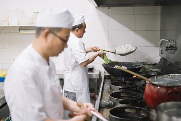 Asian chef works in the kitchen wok restaurant..