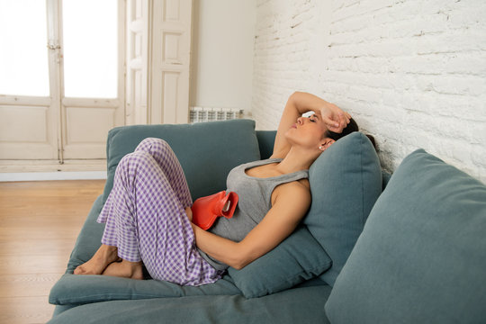 Young sad attractive woman having painful stomachache from period pain and menstrual cramps