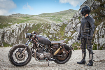 Biker with black leather suit and mask stay next his custom special rat motorbike.  Desolated mountains landscape in the background. Post apocalyptic concept