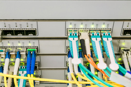 Trunk interfes of the central router. Optical links on the front panel of the network switch. Powerful computer equipment is located in the data center server room