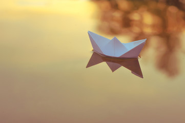 Paper origami boat floats on the surface of the water at sunset or dawn
