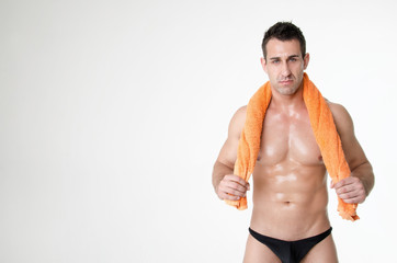 Sexy athletic man with yellow towel. Gray background.
