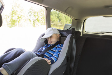 boy child sleeping in car seat in car. Road safety.