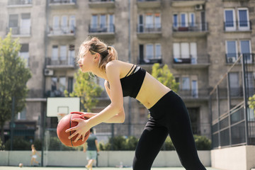 Sporty girl playing basketball