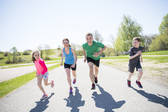 Parents with children sport running together outside