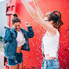 best friends having fun celebrating with confetti