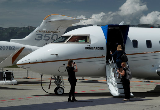 People take a picture outside a Bombardier Challenger 650 aircraft during the EBACE in Geneva