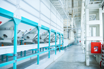 Interior of clean production workshop at food factory, modern machine units lining long hall, copy space