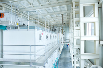High angle view at interior of clean production workshop at food factory, modern machine units lining long hall, copy space