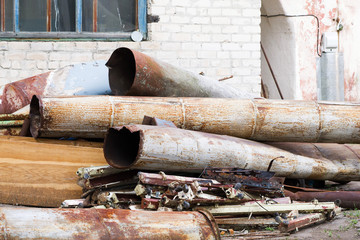 Old rusty iron pipes. Dismantling of old pipes, buildings.