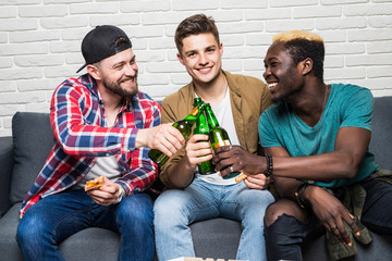 Excited young mixed race men are watching football at home with beer and pizza cheers with beer bottle.