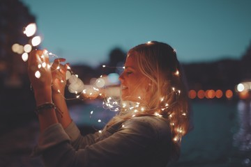 Blonde woman playing with garland fairy lights
