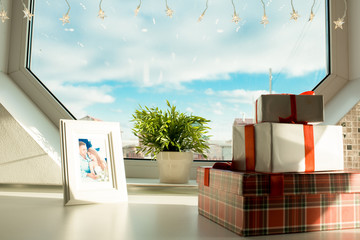 Close-up of various gift boxes and white frame with romantic photo of couple on table near geometric window with potted plant