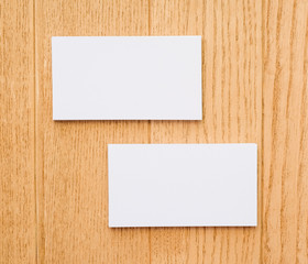 Two business cards on a wooden background background