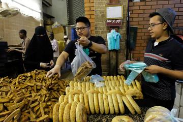 Saudi woman buys cake during Misk Foundation Jeddah Historic Festival in Saudi Arabia