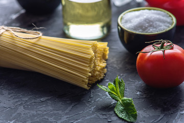 Uncooked pasta spaghetti with ingredients for tomato sauce. Concept of the composition of food design.