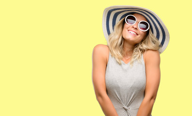 Young woman wearing sunglasses and summer hat thinking and looking up expressing doubt and wonder