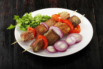 shish kebab with vegetables in plate on wooden background