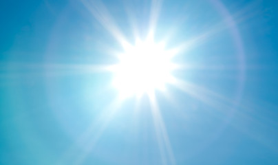 Looking up at bright, vivid sun with sunbeams and lens flare on blue summer sky