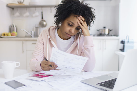 Single young african american female with many debts feeling stressed, calculating finances, siting at kitchen table with papers, trying to make both ends meet, not able to pay off utility bills