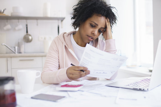 Young african american female having serious financial problems, feeling stressed while managing family budget at kitchen table